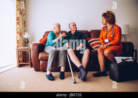 Älteres Ehepaar im Gespräch mit ihrem Mitarbeiter zu Hause. Sie sind Sittig auf dem Sofa im Wohnzimmer. - Stockfoto