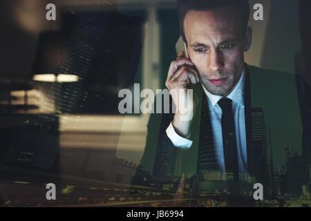 Der müde Geschäftsmann im Büro sitzen und mit Smartphone zu kommunizieren. - Stockfoto