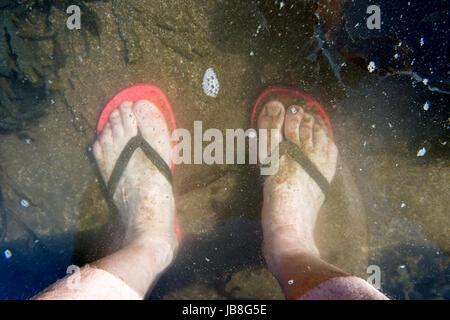 Zwei Füße in einem Rock Pool am Meer - Stockfoto