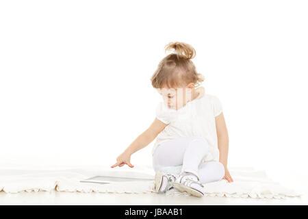 Kleines hübsches Kind spielt mit Tablet-Computer auf einem weißen Hintergrund. Lernen Spielzeug und frühen Entwicklung. - Stockfoto