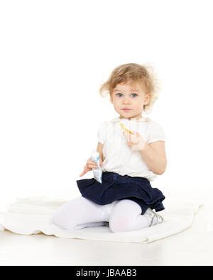 Kleines hübsches Mädchen sitzt auf dem Boden mit Zahnbürste und Zahncreme auf weißem Hintergrund. - Stockfoto