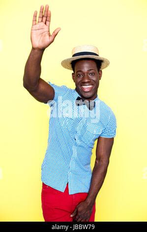 Lässige jungen afrikanischen Mann posiert mit erhobenem Arm. Hut und coole Kleidung tragen - Stockfoto