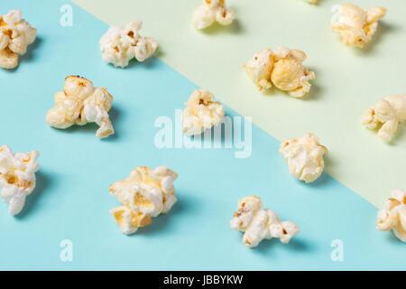 Das Popcorn in Pappbecher auf grünen und blauen Hintergrund. - Stockfoto