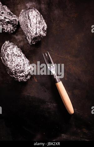 Gegrillte Folie eingewickelt Kartoffeln noch in ihrer Verlegung auf eine alte Schieferoberfläche mit Gabel und Exemplar, - Stockfoto
