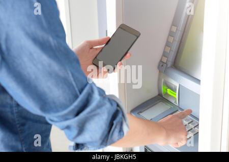 Mann mit seiner Kreditkarte in einem Geldautomaten für Bargeldbezug mit Smartphone - Stockfoto