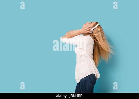 Junge Frau mit Kopfhörern hört die Musik und ruft hinein - Stockfoto