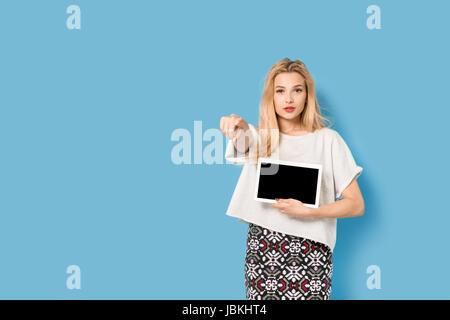 Blondes Mädchen mit Tablet-pc ist etwas mit dem Finger zeigen. - Stockfoto