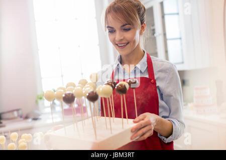 Lächelnd weibliche Caterer backen Kuchen pops in Küche - Stockfoto