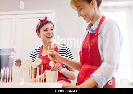 Lächelnde Frau Cateringservice backen, machen Cupcake erscheint in Küche - Stockfoto