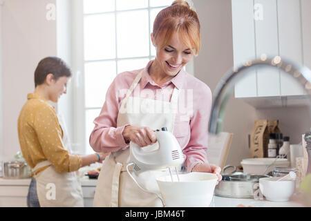 Lächelnd weibliche Caterer backen, mit elektrischen Handmixer in Küche - Stockfoto