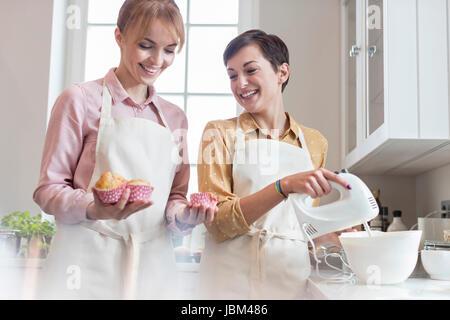 Lächelnd weibliche Caterer Backen Muffins in Küche - Stockfoto