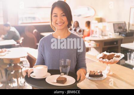 Porträt lächelnd Kellnerin mit Tablett mit Cappuccino, Brownie und Wasser im café - Stockfoto