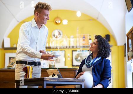 Menschen in Cafeteria mit Barkeeper servieren Espresso Kaffee, schwanger Geschäftsfrau mit Ipad am Tisch sitzen - Stockfoto