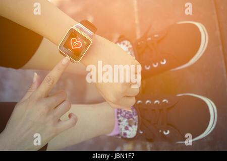 Vogelperspektive Blick auf weibliche Zeigefinger Taste auf Smartwatch mit Herzfrequenz-app beim Sitzen auf einer - Stockfoto