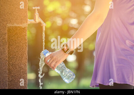 Nahaufnahme des weiblichen Hand tragen smart Watch und gießen Wasser in Plastikflasche auf Wasserhahn im Park. Natur, - Stockfoto