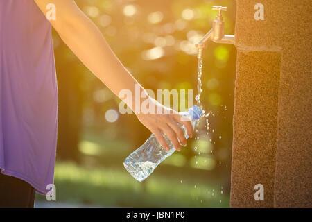 Nahaufnahme des weiblichen Hand strömenden Trinkwasser in Plastikflasche auf Wasserhahn im Park. Natur, Sommer. - Stockfoto