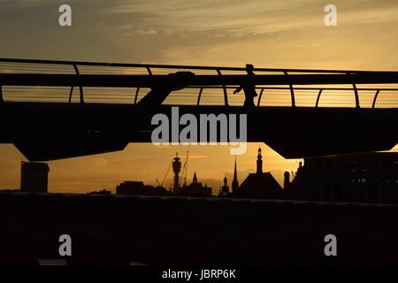 London, UK. 12. Juni 2017. Menschen sind den Sonnenuntergang hinter der Millennium Bridge in London, UK Silhouette. - Stockfoto