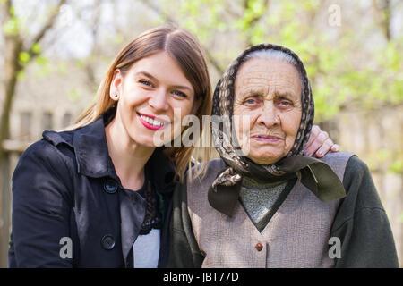 Bild von einem kranken älteren Frau posiert mit ihr glücklich Hausmeister outdoor - Stockfoto