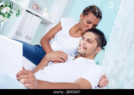 Bild des jungen Mädchens küssen ihren Freund mit laptop - Stockfoto