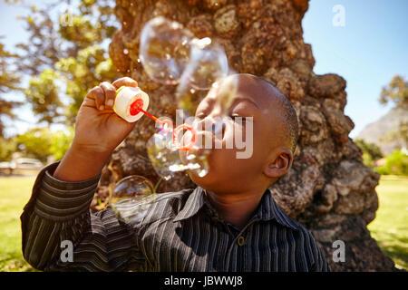 Boy bläst Luftblasen im park - Stockfoto