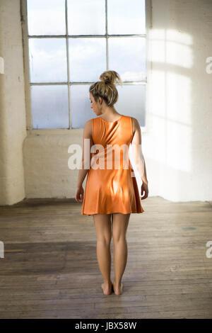Rückansicht eines jungen kaukasischen Frau trägt einen kurzen orange Sommer Kleid stehen am Fenster - Stockfoto