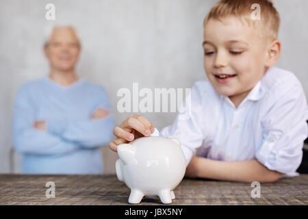 Süße begeistert junge, eine Münze in ein Sparschwein - Stockfoto
