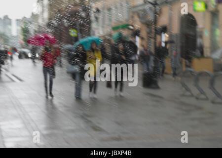 Abstrakte Stadtstraße durch Regentropfen auf Fensterglas gesehen. Mädchen in bunten Kleidern unter Sonnenschirmen - Stockfoto