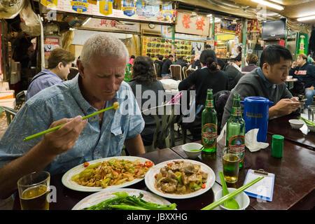 Horizontale Ansicht in einem belebten Streetfood-Restaurant in Hong Kong, China. - Stockfoto
