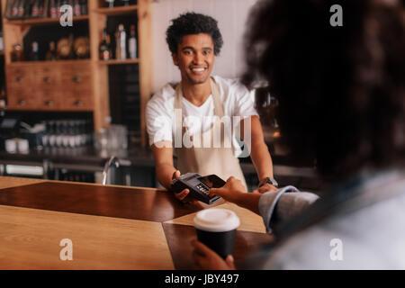 Weibliche Kunden, Zahlung per Handy am Schalter im Café mit jungen Mann. Barista Holding Kreditkarte lesen Maschine - Stockfoto