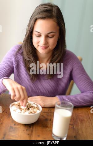 Teenager-Mädchen essen gesundes Müsli mit Joghurt zum Frühstück Diät - Stockfoto