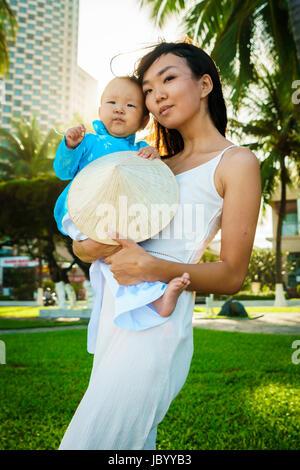 Eine Mutter hält ihre kleine Tochter in traditionelle Vietnam Kleidung Aodai in ihren Armen am Strand in der Nähe von Palmen