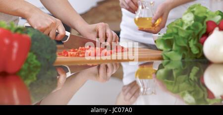 Nahaufnahme der vier menschlichen Hände sind in einer Küche kochen. Freunde, die Spaß beim frischen Salat vorbereiten. - Stockfoto