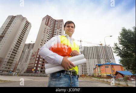 Porträt des jungen Bauingenieur in Warnweste mit Bauarbeiterhelm - Stockfoto