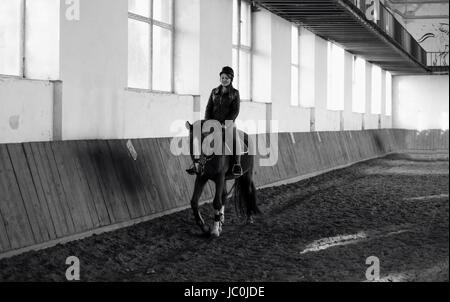 Monochrome Foto Frau Reitpferd in indoor manege - Stockfoto