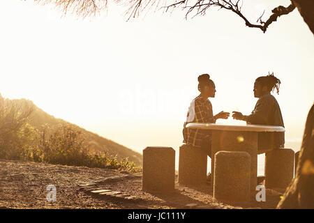 Silhouette eines jungen Paares machen einen Toast während des Sonnenuntergangs - Stockfoto