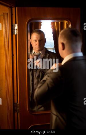 Getönten Porträt eines eleganten Gentleman suchen in Spiegel und Ankleiden - Stockfoto