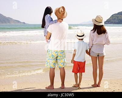 asiatischen Familie mit zwei Kindern, die mit Blick auf das Meer, Rückansicht. - Stockfoto