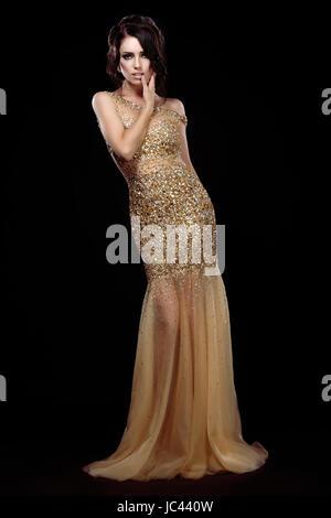 Eleganz. Aristokratischen Lady in goldenen langes Kleid auf schwarzem Hintergrund - Stockfoto