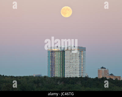 Vollmond in den Abendhimmel über städtische Häuser im Sommer - Stockfoto