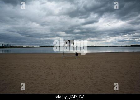 Eine Person sitzt zusammengekauert in der Nähe des Rettungsschwimmer Standes am Strand in der Nähe von Castle Island, - Stockfoto