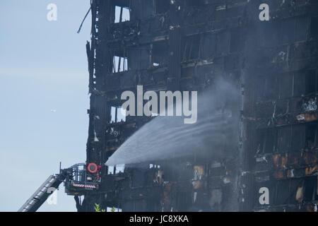 London, UK. 14. Juni 2017. Ansicht der Feuerwehr gießen Wasser auf schwelende Reste von Grenfell Turm in West-London, - Stockfoto