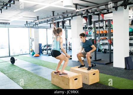Young passen paar Training im Fitness-Studio, Feld Sprünge zu tun. - Stockfoto