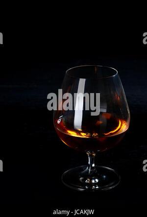 Glühende Cognac oder Weinbrand in einem Cognac-Schwenker steht auf einem dunklen Theke in einem Nachtclub in den - Stockfoto
