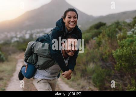 Hübscher junger Mann mit seiner Freundin auf Rücken. Paar genießt Huckepack Reiten in der Landschaft. - Stockfoto