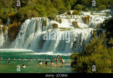 KRKA, KROATIEN - 17. AUGUST 2014. Touristen-Bad unter dem Krka Wasserfälle im Krka-Nationalpark, die große Attraktion - Stockfoto