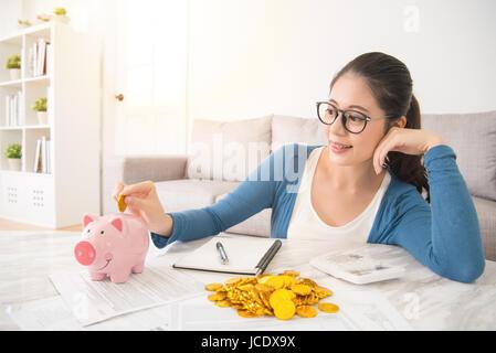 junge Mischlinge Asiatin Kaution gold Münze ins Sparschwein für das zukünftige Leben auf Sofa im Wohnzimmer zu Hause - Stockfoto