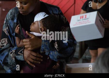 London, UK. 15. Juni 2017. Eine Frau hält ihr Kind wie sie Freiwillige Sortierung durch gespendete Kleidung am 15. - Stockfoto