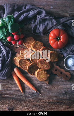 Kichererbsen-Krapfen, Karotten, Tomaten und Radieschen auf einem rustikalen Holztisch - Stockfoto