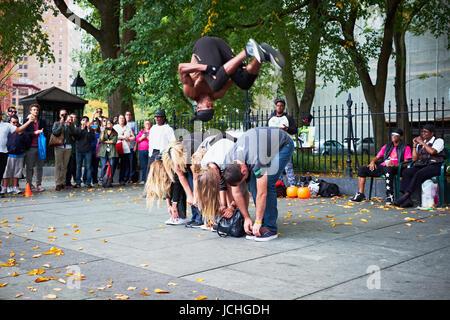 NEW YORK CITY - 18. Oktober 2014: ein Mann aus einer Performance-Gruppe macht einen Salto über eine Reihe von Touristen - Stockfoto