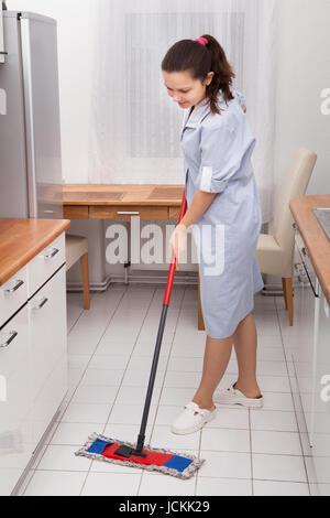 Porträt der jungen Mädchen In Uniform Reinigung Küchenboden - Stockfoto
